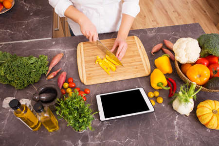 food technology: Woman cutting vegetable in pieces