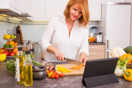 woman cooking: Woman cutting vegetables in kitchen with tablet in front of her Stock Photo