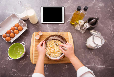 Woman preparing dough from recipe on her tablet Stockfoto