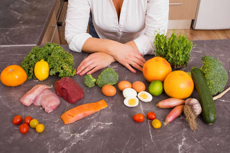 Donna in cucina con diversi cibi crudi