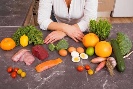Femme dans la cuisine avec différents aliments crus Banque d'images - 50800303