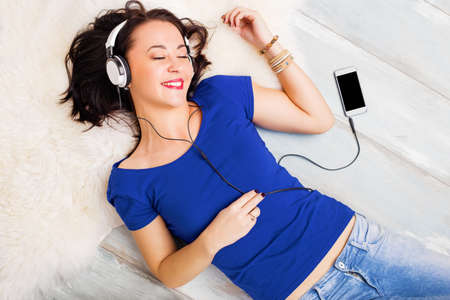 woman laying: Woman laying on the ground and listening music