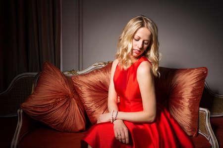 flyaway: Portrait of pretty woman sitting in red dress Stock Photo