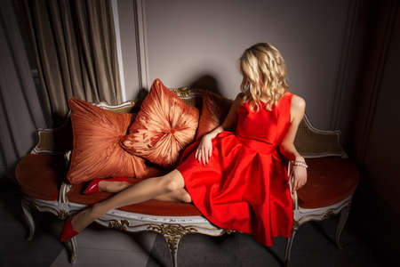 piernas con tacones: Mujer atractiva en vestido rojo pone en el sofá de lujo