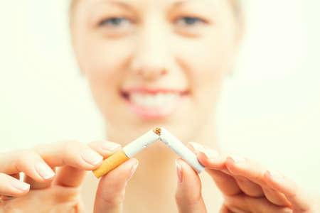 break free: Happy woman breaking cigarette Stock Photo