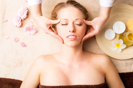 acupressure hands: Beautiful young woman receiving facial massage with closed eyes at spa studio