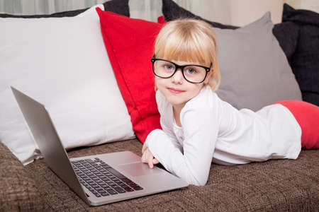 colegiala: Child with glasses lying on couch with laptop in front of her
