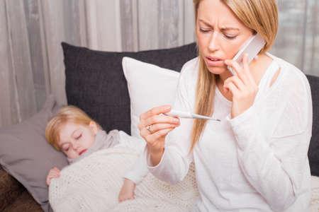 Mãe a chamar médico e que olha o termômetro Imagens
