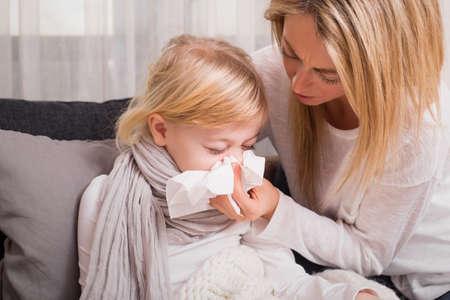 Kleines Mädchen mit Kälte und bläst ihre Nase