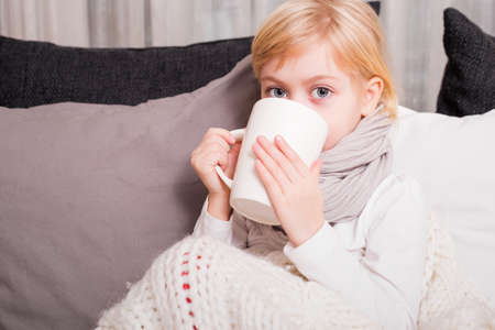 girl care: Sick child drinking tea Stock Photo