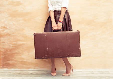 mujer con maleta: Mujer que sostiene la maleta antigua para viajar Foto de archivo