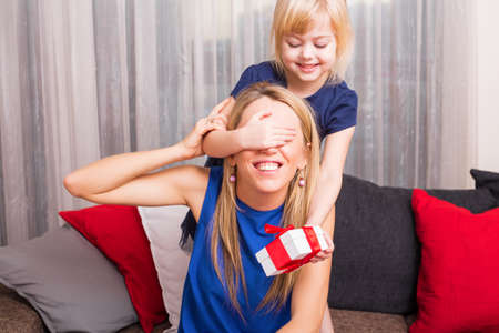 portrait woman: Little girl surprising her mother Stock Photo