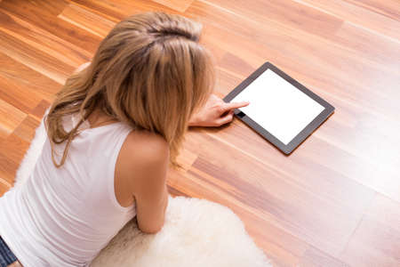ground floor: Woman lying on the ground with tablet