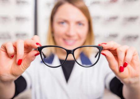 doctor giving glass: Optometrist suggesting glasses