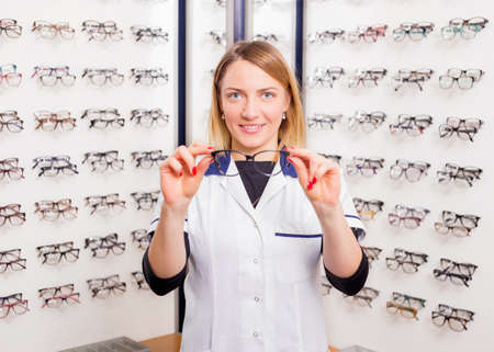 doctor giving glass: Sales assistant offering modern glasses Stock Photo