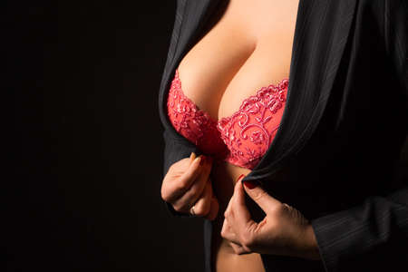 tits: Woman with big breasts getting dressed Stock Photo