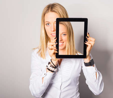 Woman standing with portable device in her hands Stock Photo