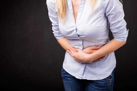 dolor de estomago: Mujer sosteniendo su estómago