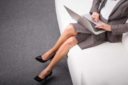 膝の上にコンピューターが付いているソファーの上に座ってかかとの高いビジネス ・ ウーマン