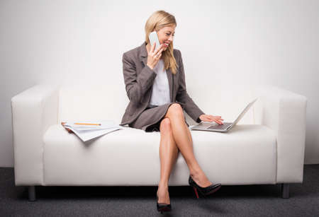 Business woman sitting on white sofa and talking on the phone
