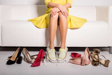 Woman sitting on couch and trying on shoes Foto de archivo