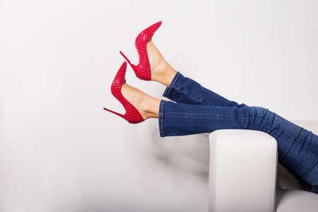 tacones rojos: Piernas femeninas en pantalones vaqueros y tacones rojos