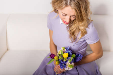 innocent: Innocent and beautiful woman with flowers sitting on couch