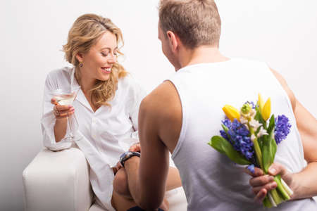 seducing: Man with flowers behind his back surprising woman Stock Photo