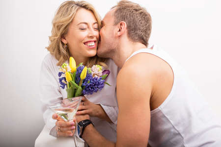 kiss love: Man giving flowers and kissing girlfriend on her cheek