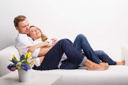 cuddling: Happy couple relaxing on couch Stock Photo