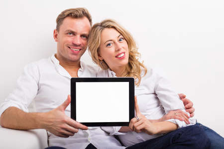 young add: Couple holding blank screen tablet Stock Photo