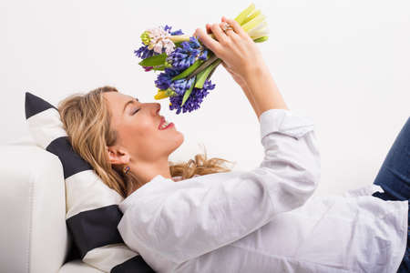 noses: Woman lying on couch and smelling flowers