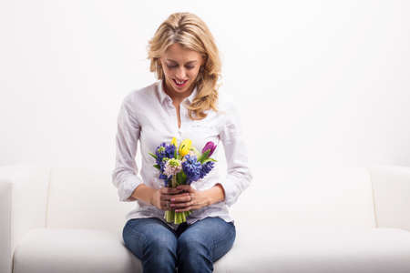 one woman: Woman sitting on sofa and looking at pretty flowers