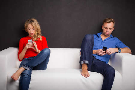 pareja enojada: Pareja sentada en el sofá con sus teléfonos en sus manos