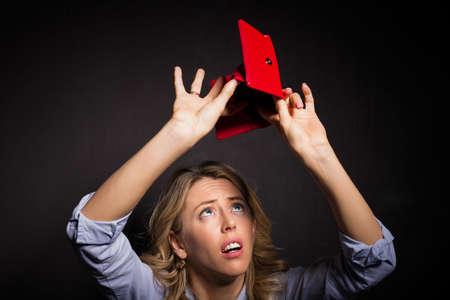 Vrouw op zoek naar geld in haar portemonnee Stockfoto