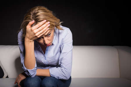 a situation alone: Depressed woman pressing her hand against her forehead