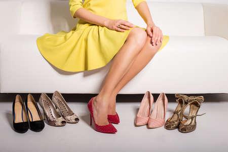 Vrouw zittend op de bank en te kiezen wat schoenen te dragen
