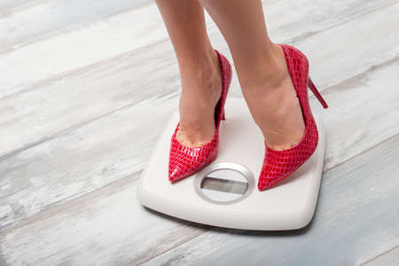 high scale: Woman with red high heels on weight scale Stock Photo