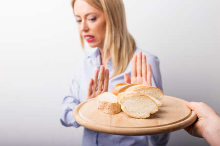 Woman refusing to eat bread Imagens