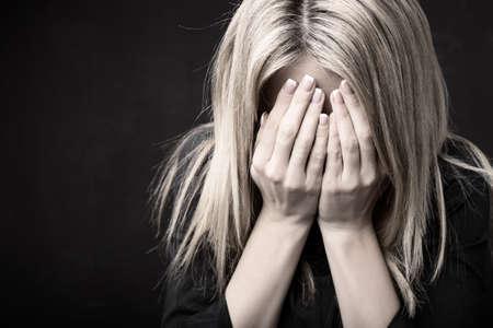 violencia: Cerca de la mujer sosteniendo su cara en sus manos Foto de archivo