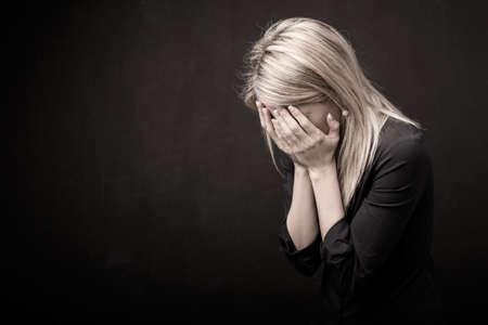 Frau hält ihr Gesicht in ihren Händen Lizenzfreie Bilder
