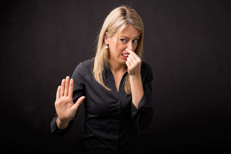 yuck: Woman holding her nose in disgust and holding her hand out Stock Photo