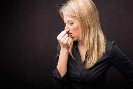 yuck: Woman holding her nose in disgust