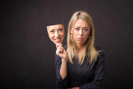 dva: Žena držící masku její šťastné tváře Reklamní fotografie