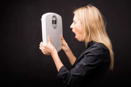 woman looking: Woman looking at weight scale in shock Stock Photo