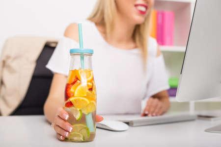 bebida de la mujer en la oficina de haber re-refrescamiento