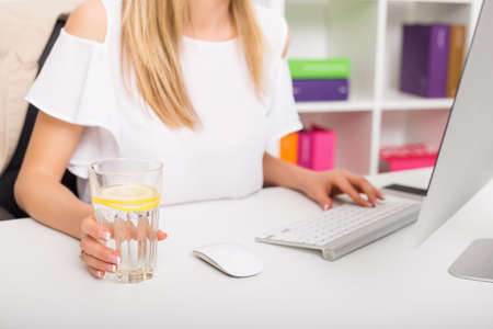 empleados trabajando: Woman drinking water while working at the office Foto de archivo