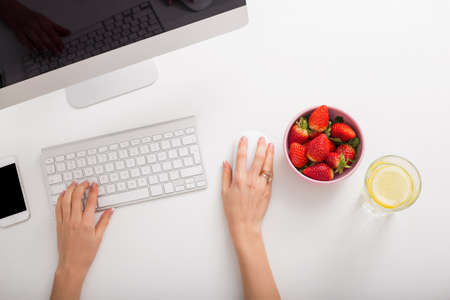 stationary: Strawberries and lemon water on office table