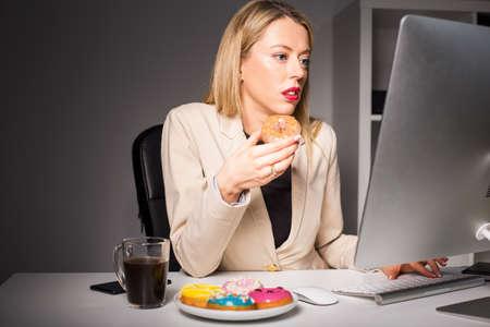Vrouw in het kantoor van het eten van junk food