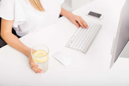 empleados trabajando: Mujer que tiene el agua de limón mientras se trabaja